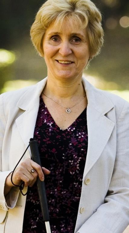 Małgorzata Pacholec - dyrektor Instytutu Tyflologicznego. Stoi w parku, w ręku trzyma laskę.