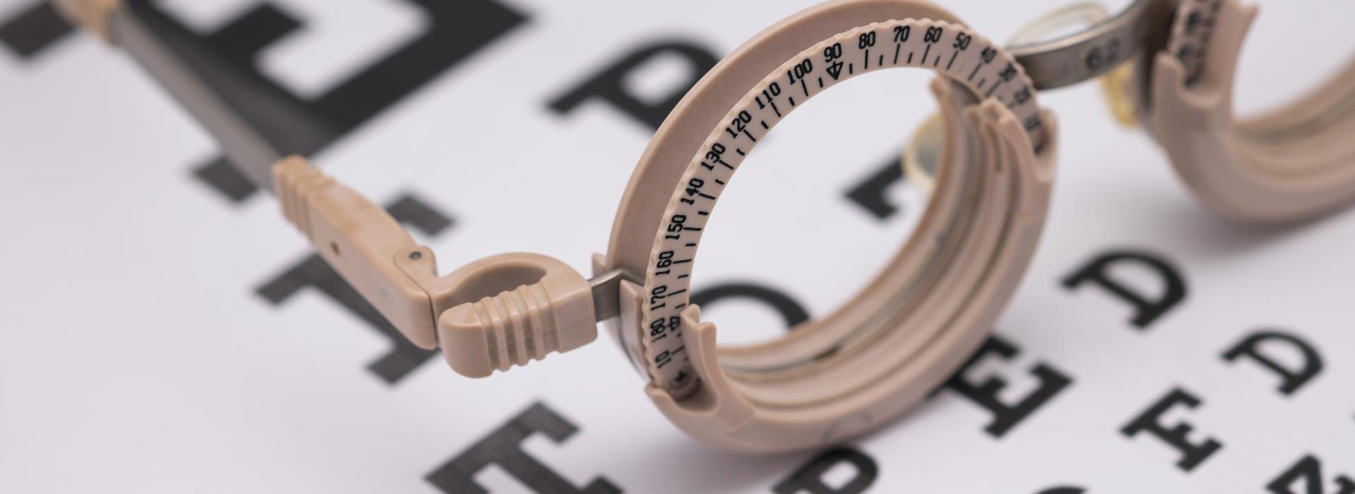 Okulary korekcyjne leżące na tablicy okulistycznej