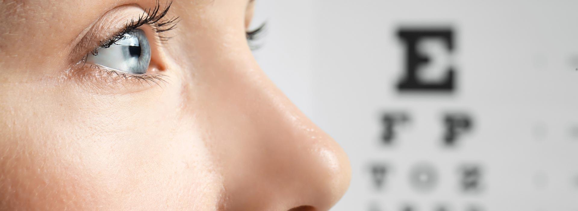 Badanie wzroku - profil młodej kobiety, w tle tablica okulistyczna