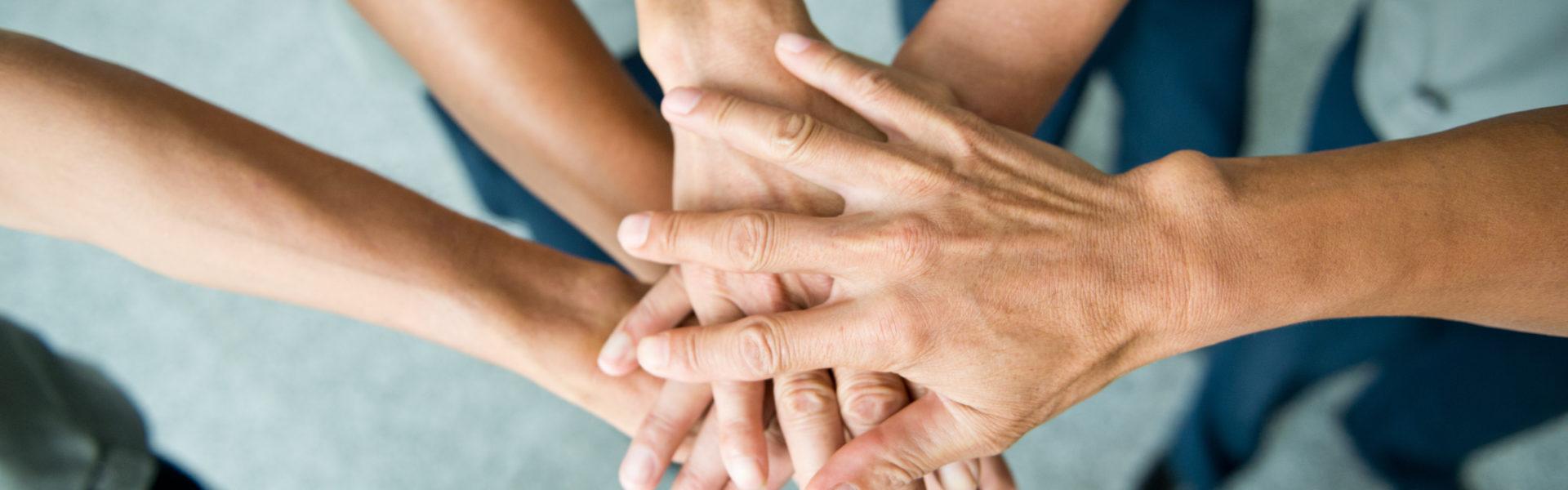 Dłonie kilku osób położone jedna na drugiej