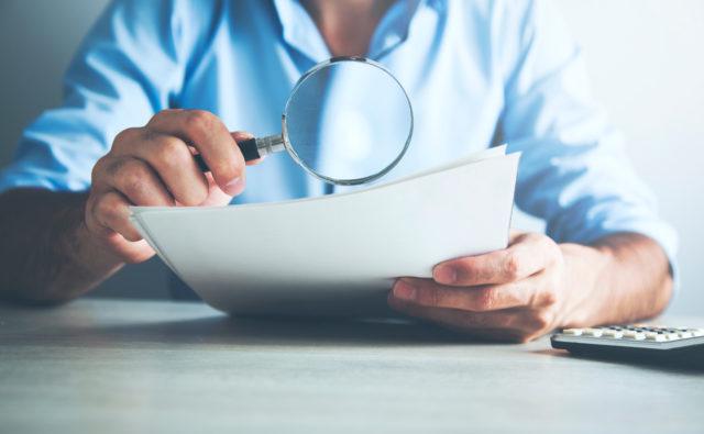 Osoba czyta tekst, korzystając z lupy.