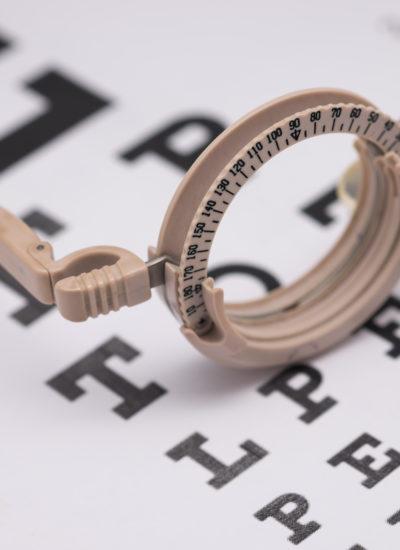 Na tablicy Snellena (okulistycznej) leżą okulary do badania wzroku.
