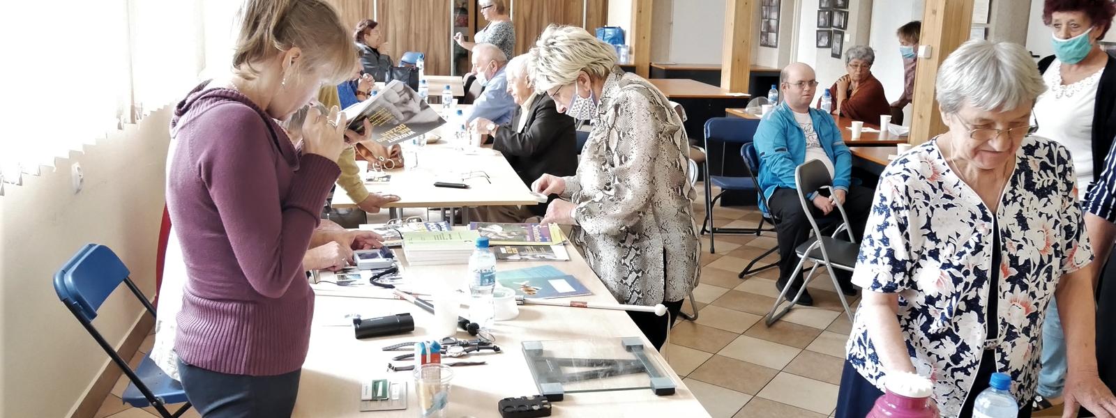 Sala szkoleniowa. Na stole leżą pomoce optyczne. Uczestnicy szkolenia oglądają je i sprawdzają, w jaki sposób działają.