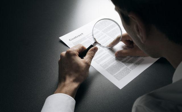 Mężczyzna czyta dokument za pomocą lupy.