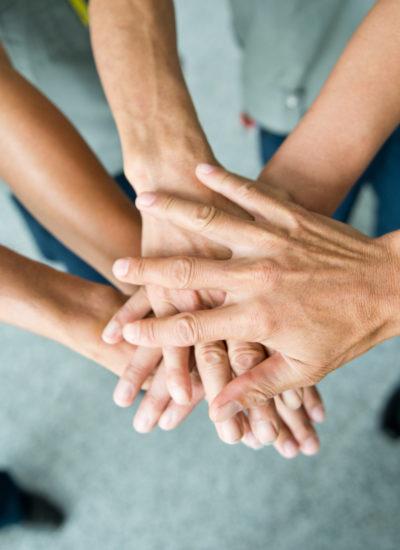 Dłonie kilku osób położone jedne na drugich.