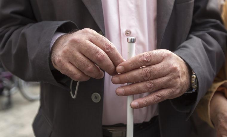 Mężczyzna trzyma w dłoni białą laskę. Fot. Shutterstock.